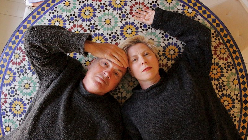 husband and wife Tim and Lee Friese-Greene lying on a mosaic tiled floor